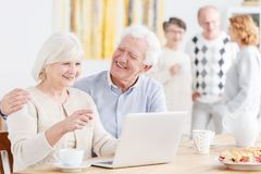 Senior life insurance concept. Elderly couple sitting with laptop at the table, senior men embracing smiling woman Stock Photos