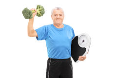 Senior lifting a broccoli dumbbell Royalty Free Stock Photos