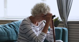 Senior lonely woman sitting alone at home holding walking stick