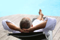 Senior in long chair enjoying sun bath Royalty Free Stock Image