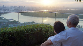 Senior looking at sunrise together over city skyline Royalty Free Stock Images
