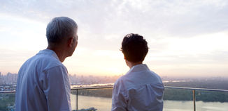 Senior looking at sunrise together over city skyline Stock Image