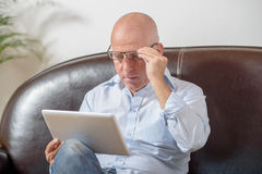 A senior  looks at a digital tablet Royalty Free Stock Photography