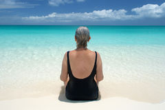 Senior looks out on ocean from serene beach in the Caribbean Stock Image
