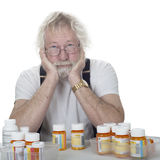 Senior with lots of prescriptions. Senior wearing glasses with a lot of prescription bottles of pills isolated on white Royalty Free Stock Photos