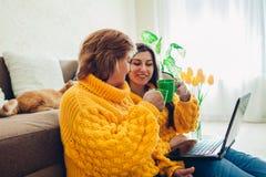 Senior macierzysty i jej dorosła córka używa laptop w domu podczas gdy pijący herbaty Macierzysty ` s dnia poj?cie zdjęcie stock