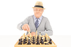Senior making a move on a chessboard Stock Photos