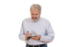 Senior Making Notes. Senior man making notes in notebook set against a white background Stock Photos