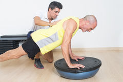 Senior making push ups. Coach helps elderly men with push ups exercise Stock Photo