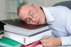 Senior male accountant sleeping on table fotos de archivo