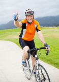 Senior male bicyclist. Happy senior male bicyclist giving thumb up on bicycle royalty free stock photography