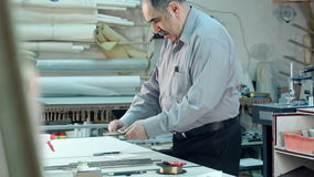 Senior male business owner working in workshop of his frame studio. Professional shot in 4K resolution. 083. You can use it e.g. in your commercial video stock footage