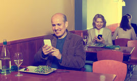 Senior male businessman with food and smartphone Stock Image