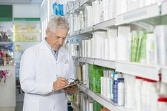 Chemist Writing On Clipboard While Standing By Shelves. Senior male chemist writing on clipboard while standing by shelves in pharmacy Royalty Free Stock Images
