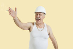 Senior male constructor shouting over yellow background Stock Image