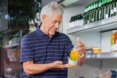 Senior Male Customer Buying Juice Bottle. Senior male customer reading information on juice bottle at supermarket Royalty Free Stock Image