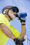 Senior Male Cyclist Drinking Water. Low angle view of a senior male cyclist drinking water against sky Royalty Free Stock Photos