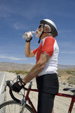 Senior Male Cyclist Drinking Water. Side view of a senior male cyclist drinking water Royalty Free Stock Images
