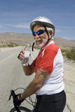 Senior Male Cyclist Holding Water Bottle Stock Image