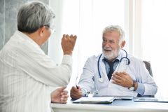 Senior male Doctor and Asian male patient are talking. Stock Image