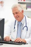 Senior male doctor at desk Stock Photo