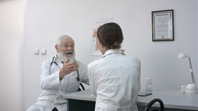 A senior male doctor at a desk in an office smiling and talking to female doctor. stock footage