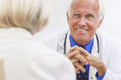 Senior Male Doctor With Elderly Female Patient. A senior male doctor sitting at a desk in an office wearing a shirt, tie and stethoscope talking to an elderly stock photo