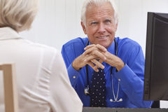 Senior Male Doctor With Female Patient. A smiling senior male medical doctor with a female patient and computer at his desk in an office at a hospital royalty free stock photography