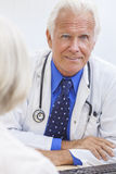 Senior Male Doctor With Female Patient Stock Photos