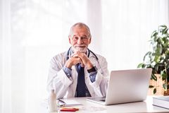 Senior doctor with laptop sitting at the office desk. Stock Images