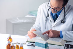 Senior Male Doctor looking for Information in a Medical Book at Royalty Free Stock Images