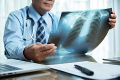 Senior Male doctor looking to x-ray film. Asian Senior Male doctor in blue shirt looking to x-ray film at a medical room royalty free stock image