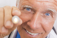Senior Male Doctor With Pen Light royalty free stock photos
