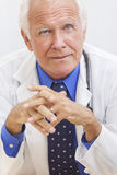 Senior Male Doctor With Stethoscope. A senior man male medical hospital doctor sitting at a desk wearing a shirt, tie and stethoscope stock image