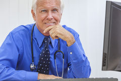 Senior Male Doctor With Stethoscope. A senior man male medical hospital doctor sitting at a desk wearing a shirt, tie and stethoscope stock photo