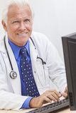 Senior Male Doctor With Stethoscope. A senior man male medical hospital doctor sitting at a desk wearing a shirt, tie and stethoscope royalty free stock photos