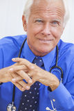 Senior Male Doctor With Stethoscope at Desk. A senior male doctor sitting at a desk in an office wearing a shirt, tie and stethoscope royalty free stock photography