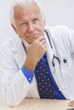 Senior Male Doctor With Stethoscope at Desk. A senior male doctor sitting at a desk in an office with a computer, wearing a shirt, tie and stethoscope stock photography