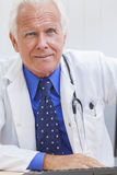 Senior Male Doctor With Stethoscope at Desk & Computer. A senior male doctor sitting at a desk in an office with a computer, wearing a shirt, tie and stethoscope royalty free stock images