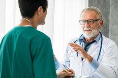 Senior male doctor working with another doctor.