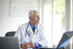 Senior male doctor working at desk in the specialist office. Portrait of male doctor looking thoughtfully while sitting consulting room and writing down the Stock Images