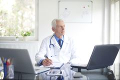 Senior male doctor working at desk in the specialist office. Portrait of male doctor looking thoughtfully while sitting consulting room and writing down the Royalty Free Stock Photos