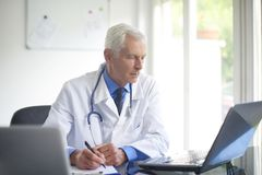 Senior male doctor working at desk in the specialist office. Portrait of male doctor writing down the diagnosis while sitting at consulting room Royalty Free Stock Image