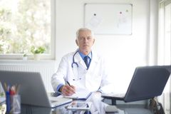 Senior male doctor working at desk in the specialist office. Portrait of male doctor writing down the diagnosis while sitting at consulting room Stock Photography