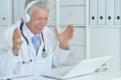 Doctor working with laptop. Senior male doctor working with laptop at his office Stock Photo