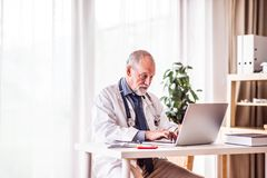 Senior doctor with laptop working at the office desk. Royalty Free Stock Images