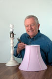 Senior male doing home repair - lamp Stock Photos