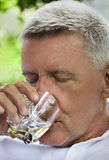 Senior male drinking spirits Royalty Free Stock Photos
