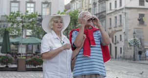 Senior male and female tourists walking in town center and looking in binoculars. Senior two male and female tourists walking in town center while traveling in stock footage