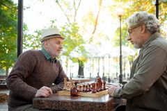 Senior male friends playing chess in the nature. What can you do now. Side view of sly old men smiling while sitting at chessboard in park. His comrade is Royalty Free Stock Photography